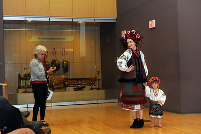 """Katerina Kermoschuk and her daughter model """"vyshyvka."""" Lecturer Natalie Kononenko narrates the fashion demonstration of the Ukrainian style of clothing.  Photo by Donn Young."""