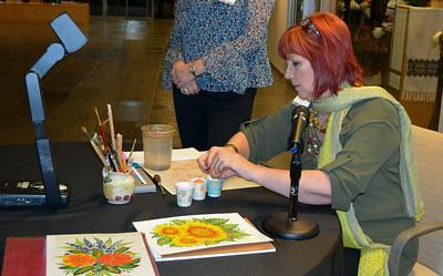 Artist Olena Zintchouk prepares tempera paint using egg yolk for her demonstration.
