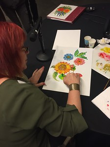 Artist Olena Zintchouk teaches the audience her technique for painting colorful wildflowers.
