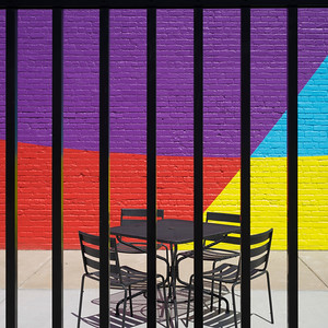 Empty chairs and table arranged on sidewalk cafe seen through metal fence, Minneapolis, Hennepin County, Minnesota, USA