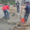 Finishing off the concrete for the Leones' house.