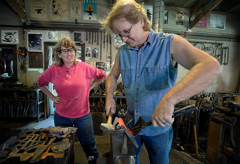 Blacksmith David Norrie hammers a piece of steel to create a curve at the edge as artist Beth Stade watches Wednesday, May 23, 2018, while the two make keepsake art made from some of the guardrails removed from U.S. 34 in the Big Thompson Canyon. (Photo by Jenny Sparks/Loveland Reporter-Herald)