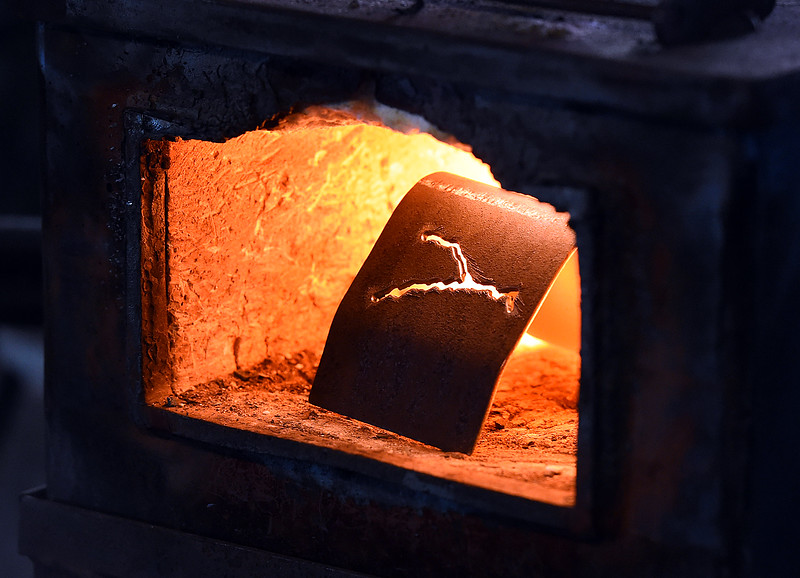 A piece of steel with an image of the Big Thompson River cut into it heats up in a forge Wednesday, May 23, 2018, at David Norrie's balcksmith shop in Berthoud. Balcksmith David Norrie is helping artist Beth Stade create keepsake art made from some of the guardrails removed from U.S. 34 in the Big Thompson Canyon. (Photo by Jenny Sparks/Loveland Reporter-Herald)