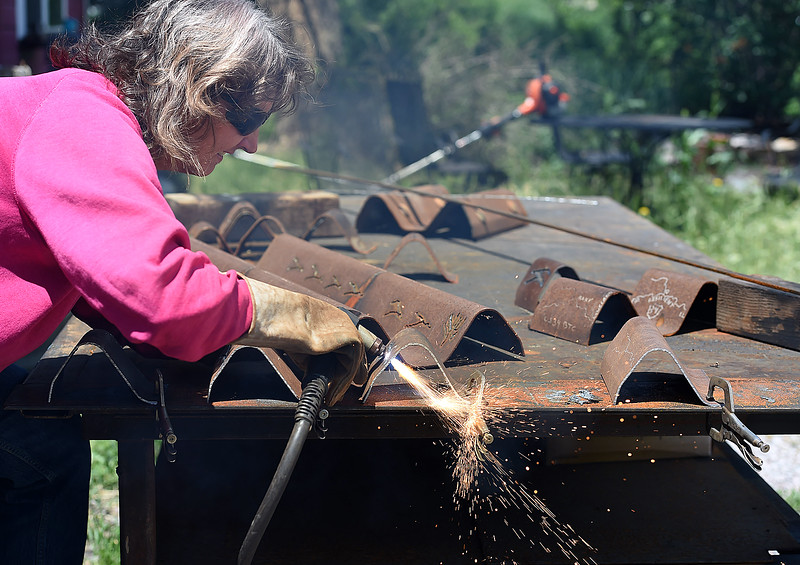 Artist Beth Stade uses a plasma cutter to cut an image of the Big Thompson River into a piece of steel on Wednesday, May 23, 2018, while creating keepsake art made from some of the guardrails removed from U.S. 34 in the Big Thompson Canyon. (Photo by Jenny Sparks/Loveland Reporter-Herald)