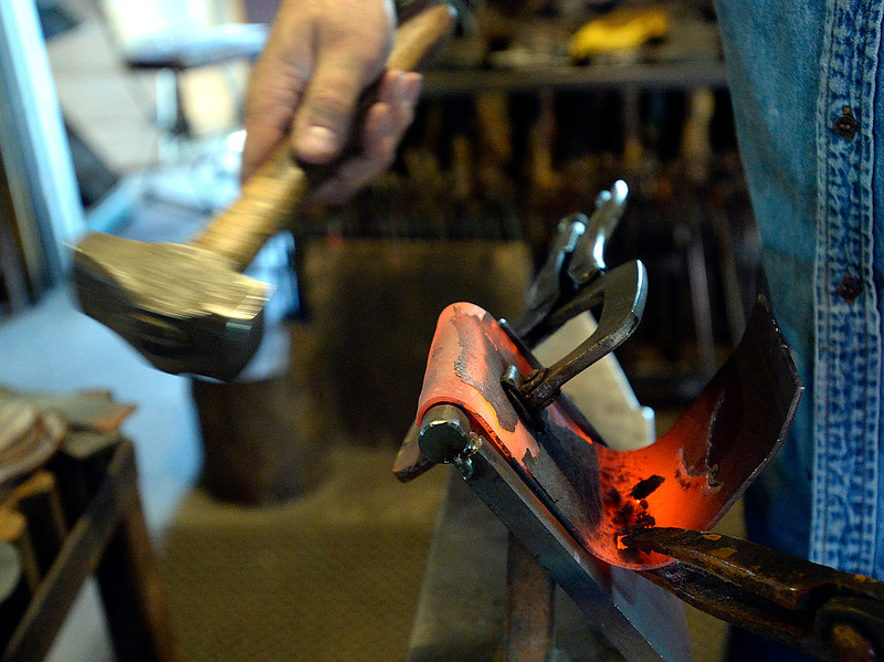 Blacksmith David Norrie hammers a red-hot piece of steel to create a curve at the edge Wednesday, May 23, 2018, while helping artist Beth Stade make keepsake art made from some of the guardrails removed from U.S. 34 in the Big Thompson Canyon. (Photo by Jenny Sparks/Loveland Reporter-Herald)