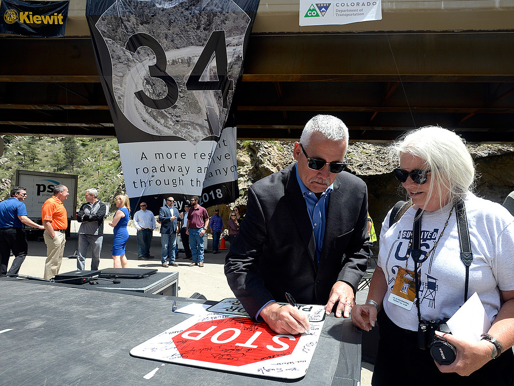 . Big Thompson Canyon resident Mary Myers, right, has Scott Cassels, left, an Executive Vice President for Kiewit Corporation, autograph the pilot car stop sign Thursday, May 31, 2018, that used to hang near her home while construction was under way to rebuild U.S. 34 during an event to celebrate the re-opening of the road west of Loveland.  (Photo by Jenny Sparks/Loveland Reporter-Herald)