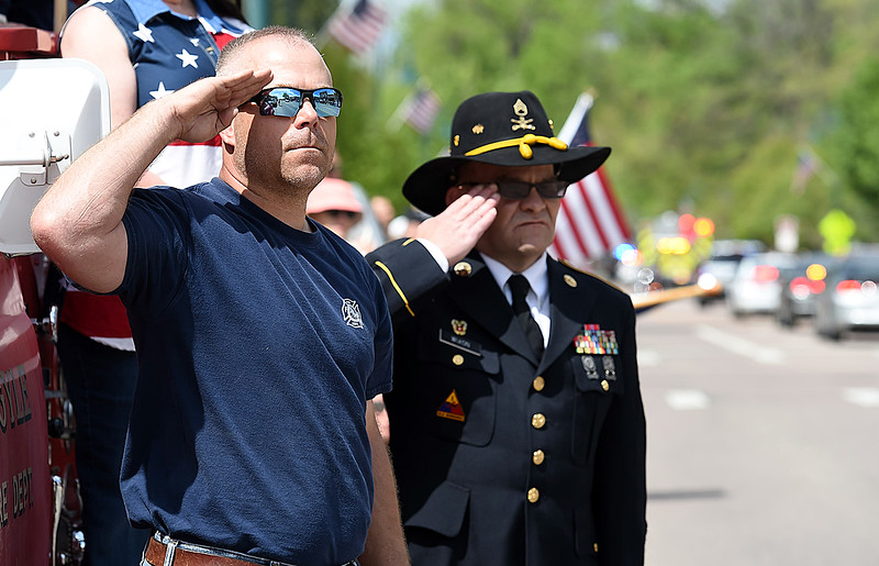 Army veterans Dana Foley, left, and Tim Wixon, right, salute as the procession carrying fallen soldier Gabriel Conde passes by them on Mountain Avenue in Berthoud on Friday, May 11, 2018, on its way to the funeral home in Longmont. Foley said Conde was like a son to him because he spent a lot of time with Foley's children.  (Photo by Jenny Sparks/Loveland Reporter-Herald)