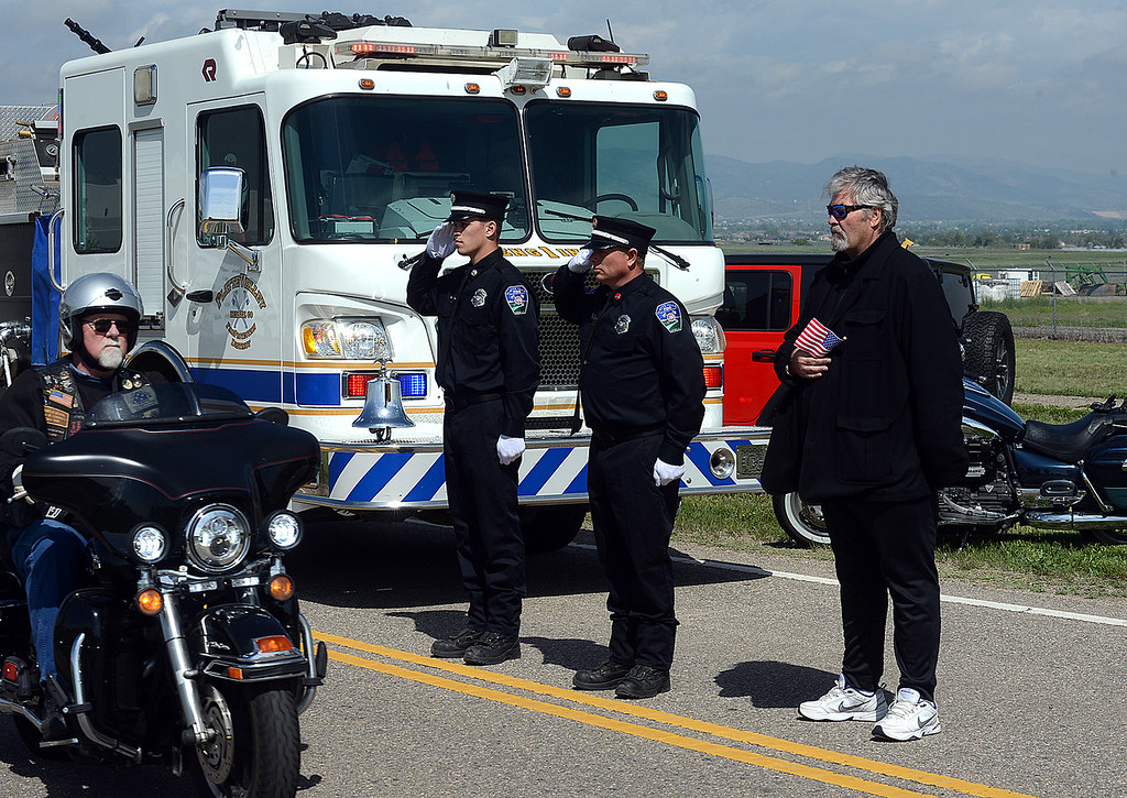. Thomas R. Johnston, right, a retired Weld County Sheriff\'s deputy, stands with Platte Valley firefighters Darin Henry, center, and Tyler Dilley as the motorcade bearing fallen soldier Gabriel Conde passes along Earhart Road from the Northern Colorado Regional Airport in Loveland on Friday morning, May 11, 2018. (Photo by Craig Young/Loveland Reporter-Herald)