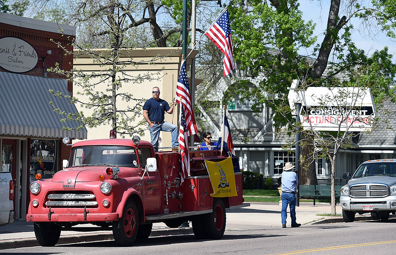 Dana Foley stands on his antique firetruck as he waits to see the procession carrying fallen soldier Gabriel Conde pass by on Mountain Avneu in Berthoud Friday, May 11, 2018, on its way to the funeral home in Longmont. (Photo by Jenny Sparks/Loveland Reporter-Herald)