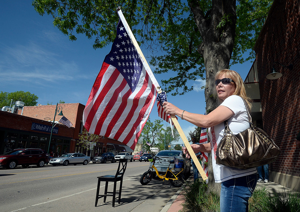 . Sharon McGonigal waits on Mountain Avenue in Berthoud to watch the procession carrying fallen soldier Gabriel Conde pass by on Friday, May 11, 2018, on its way to the funeral home in Longmont. (Photo by Jenny Sparks/Loveland Reporter-Herald)
