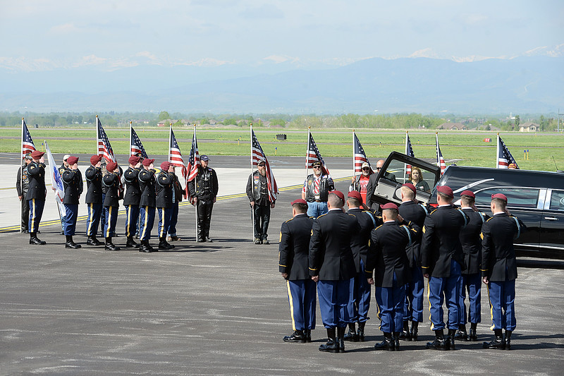 Army honor guard members salute after carrying the casket of Spc. Gabriel Conde past flag-bearing Patriot Guard Riders on Friday morning, May 11, 2018, from the airplane to the hearse on the tarmac of the Northern Colorado Regional Airport in Loveland.  (Photo by Craig Young/Loveland Reporter-Herald)