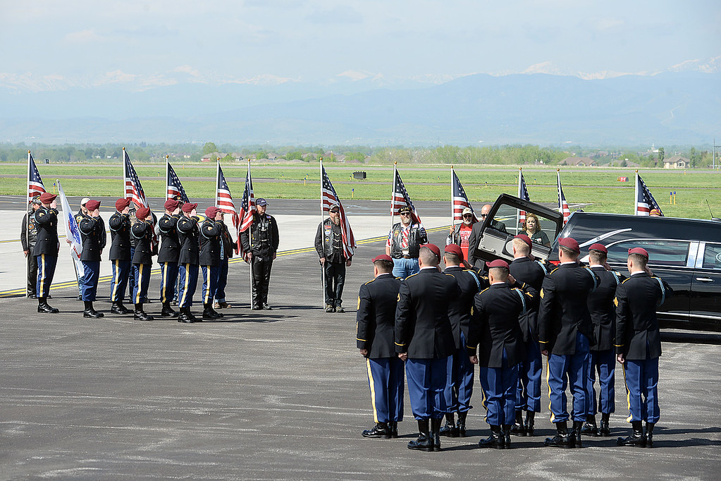 . Army honor guard members salute after carrying the casket of Spc. Gabriel Conde past flag-bearing Patriot Guard Riders on Friday morning, May 11, 2018, from the airplane to the hearse on the tarmac of the Northern Colorado Regional Airport in Loveland.  (Photo by Craig Young/Loveland Reporter-Herald)