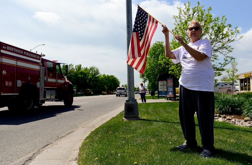 . Lenore Colpitts holds a flag as the funeral procession for U.S. Army Spc. Gabriel Conde passes on Main Street in Longmont, Colorado on May 11, 2018. (Photo by Matthew Jonas/Staff Photographer)