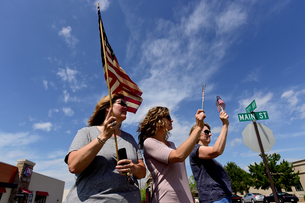 . From left: Lori Hunter, Kristen Bond and Amber Maes hold  flags as the funeral procession for U.S. Army Spc. Gabriel Conde passes on Main Street in Longmont, Colorado on May 11, 2018. (Photo by Matthew Jonas/Staff Photographer)
