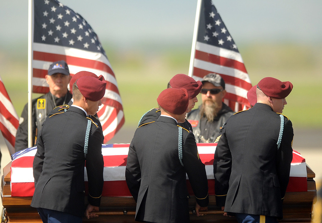 . Army honor guard members carry the casket of Spc. Gabriel Conde past flag-bearing Patriot Guard Riders on Friday morning, May 11, 2018, from the airplane to the hearse on the tarmac of the Northern Colorado Regional Airport in Loveland.  (Photo by Duncan Young/Loveland Reporter-Herald)
