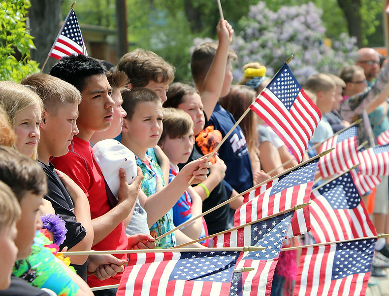 Berthoud area school children line Mountain Avenue in Berthoud waving American flags as the procession carrying fallen soldier Gabriel Conde passes by on Friday, May 11, 2018, on its way to the funeral home in Longmont. (Photo by Julia Rentsch/Loveland Reporter-Herald)