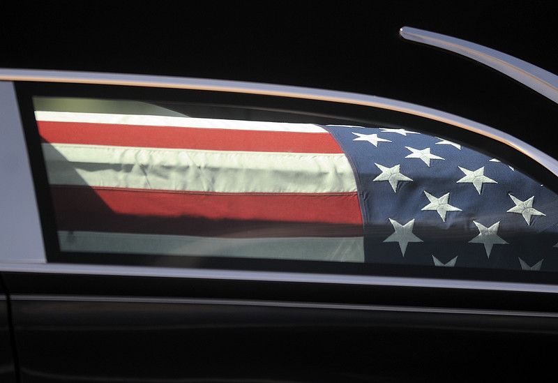 The flag-draped casket carrying the body of Spc. Gabriel Conde is seen through the window of a hearse on Friday morning, May 11, 2018, as it leaves the Northern Colorado Regional Airport in Loveland.  (Photo by Duncan Young/Loveland Reporter-Herald)