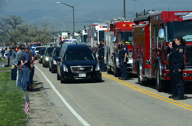 Firefighters from the region stand and salute as the hearse carrying the body of Spc. Gabriel Conde passes by on Friday morning, May 11, 2018, at the Northern Colorado Regional Airport in Loveland.  (Photo by Craig Young/Loveland Reporter-Herald)