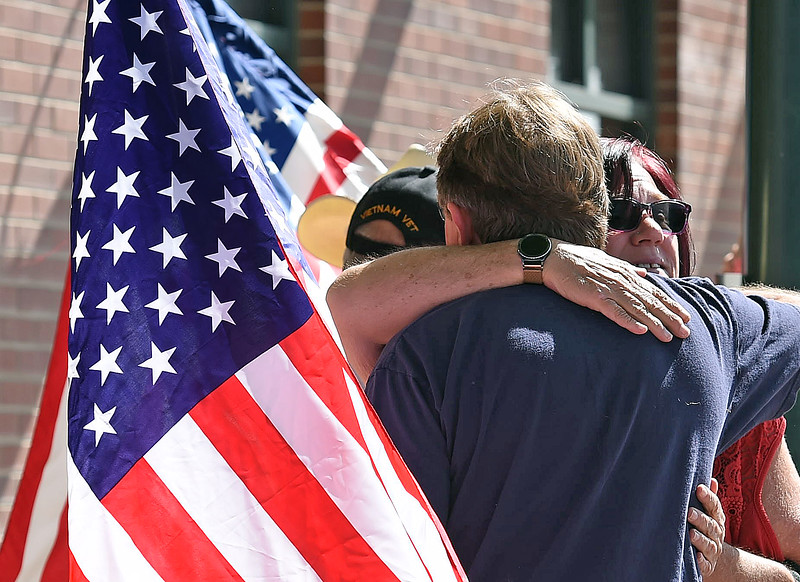 Robin LaBarbara and Scott McGonigal hug as they wait to see the procession carrying fallen soldier Gabriel Conde pass by on Mountain Avenue in Berthoud Friday, May 11, 2018, on its way to the funeral home in Longmont. (Photo by Jenny Sparks/Loveland Reporter-Herald)