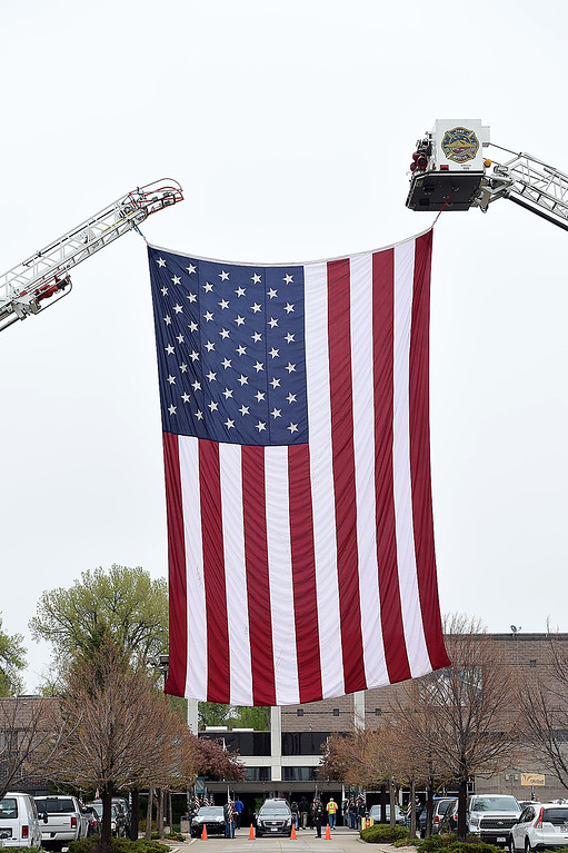 . A huge American flag hoisted by Longmont Fire Department ladder trucks flies over the entrance to Life Bridge Church during the memorial service for fallen soldier Spc. Gabriel Conde on Saturday, May 12, 2018, at LifeBridge Church in Longmont.  (Photo by Jenny Sparks/Loveland Reporter-Herald)