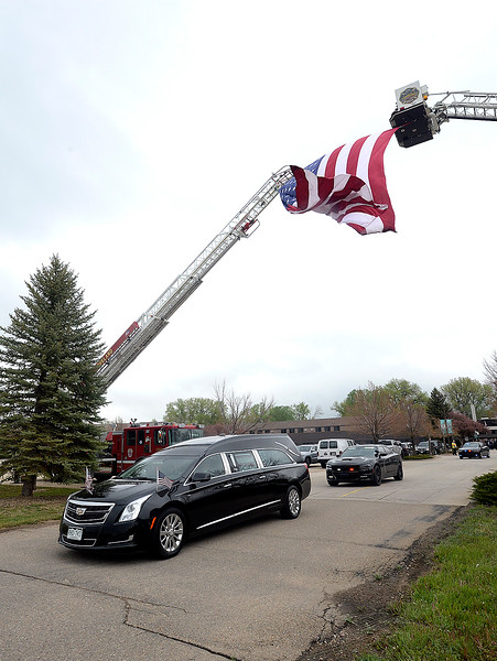 The hearse carrying the casket of Spc. Gabriel Conde drives under a huge American flag hoisted by Loveland Fire Rescue Authority and Longmont Fire Department ladder trucks as it leaves the church after his memorial service on Saturday, May 12, 2018, at LifeBridge Church in Longmont.  (Photo by Jenny Sparks/Loveland Reporter-Herald)