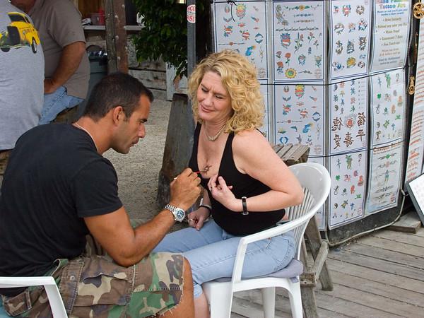 Woman Getting Breast Tattoo