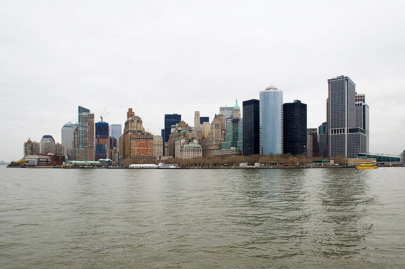 The lower Manhattan skyline as seen from the ferry while returning to Manhattan from Ellis Island, with the terminal for ferries to Liberty and Ellis Islands on the left, and the main ferry terminal for such lines as the Staten Island Ferry on the far right