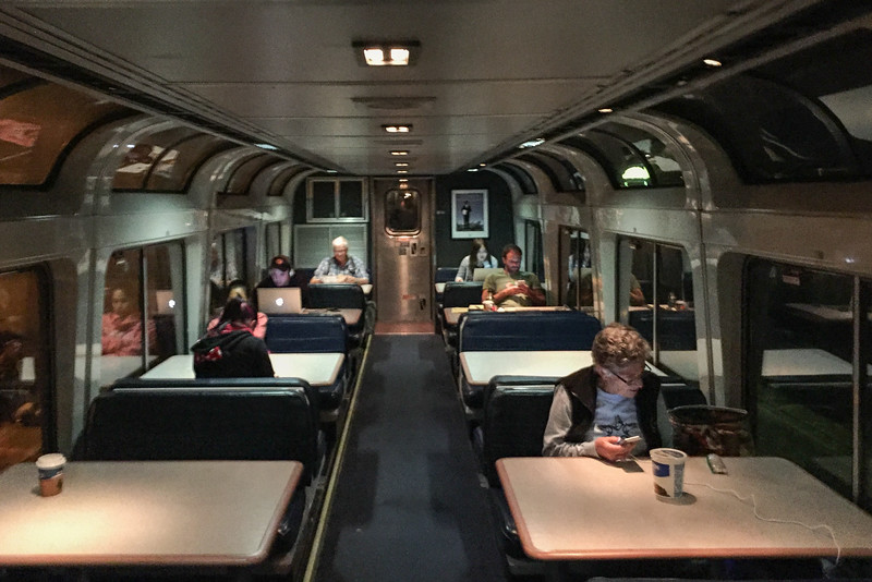 The shared Amtrak Coast Starlight Lounge Car at night. Free wifi and a place to spread out and work