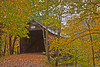 Turkey Jim's covered bridge in Campton, New Hampshire surrounded by Fall foliage in the rain