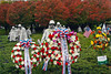 Flower wreaths on display at the Korean Memorial with colorful fall leaves in the background