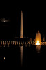 Washington Monument and full moon reflecting in fountains of World War II Memorial