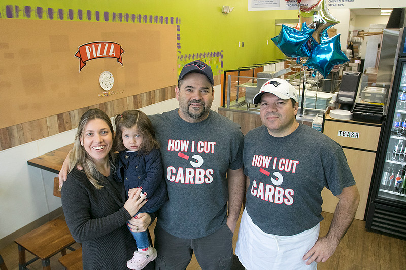 """The pizza place in Leominster """"U.S. Pizza Express"""" opened on Wednesday and they sat down to talk about their place on Friday, Nov. 22, 2019. From left is Fabiane Schiavinato, her daughter Antonella, 2, her husband and owner Pietro and their manager Geraldo Sousa. SENTINEL & ENTERPRISE/JOHN LOVE"""