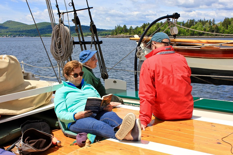woman reading on the J & E Riggin, a Maine windjammer cruise out of Rockland, Maine