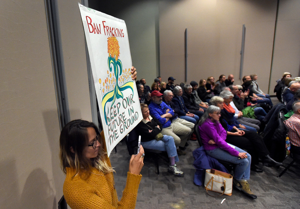 . Mirna Tufekcic holds a sign about fracking as U.S. Sen. Michael Bennet speaks during a town hall meeting at UCAR on Friday in Boulder. For more photos and a video interview with Bennett go to www.dailycamera.com Jeremy Papasso/ Staff Photographer/ May 19, 2017