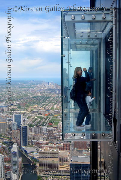 A woman standing in the observatory window at the Sears/Willis Tower.
