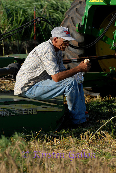 One of the truck drivers finds a nice solitary spot on a mower to sit and take his break.