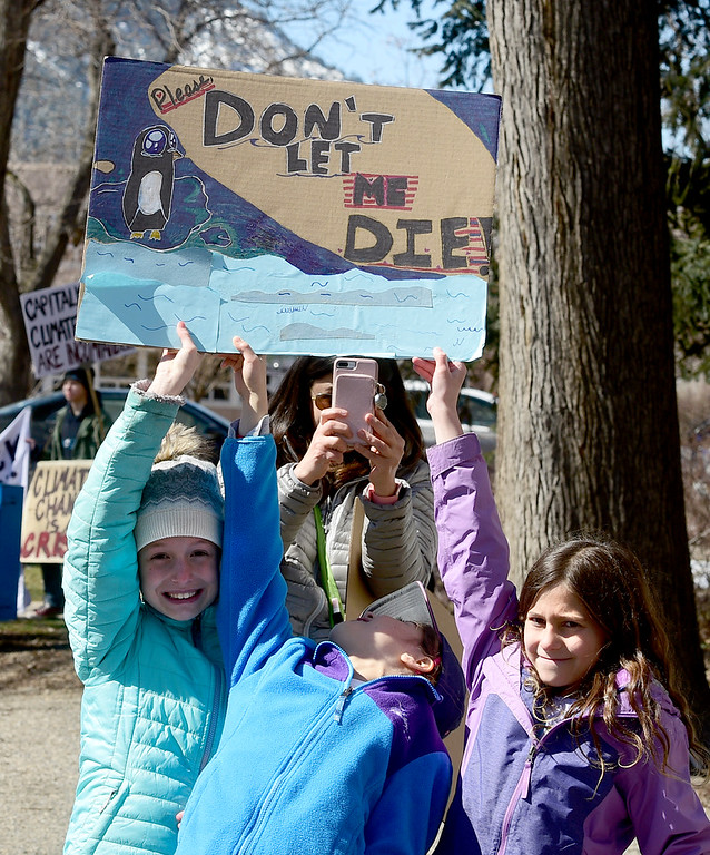. BOULDER, CO - March 15, 2019:  Aura Mortimer, left,Victoria B. and Jasmine Wine, hod up a sign hoping to protect penguins. Boulder area students as well as students from Conifer and Leadville gathered at the Central Park bandshell and marched around downtown Boulder. Around the world, thousands of young people are demanding action on climate change. Some students in Colorado are preparing to miss class Friday as part of the U.S. Youth Climate Strike. (Photo by Cliff Grassmick/Staff Photographer)