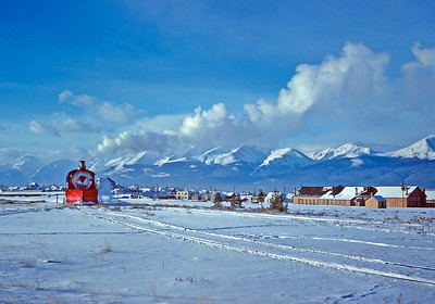 December 15, 1961.  C&S 641 backs into town to pickup its train for Climax on an absolutely glorious winter day in the Arkansas River Valley. In the background are several peaks that exceed 14,000 feet. I think one of them is Mount Elbert, the highest point in Colorado. Since originally posting the picture I have learned the large building on the right is the DRGW engine and car shop, now gone.
