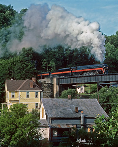 In nice light and cool morning air, the Independence Limited crosses above Bramwell, WV enroute from Bluefield, WV to Portsmouth, OH.  June 25, 1986.