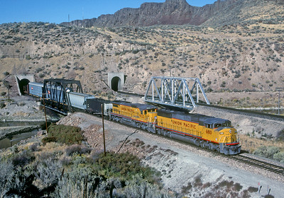October 1991.  A westbound UP train exits the tunnel just west of Palisade, Nevada in paired track territory on the SP line. The former WP line is in the background. Until 1938 the ng. Eureka and Palisade crossed both lines at grade right at the tunnel portals.