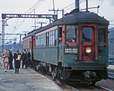 March 1962.  A northbound train stops at Great Lakes depot. This is a highly cropped version of a broader scene, which explains the grain. But I like the cropped version because it highlights the people, and the grain perhaps reflects the photographic technology and style of the time.
