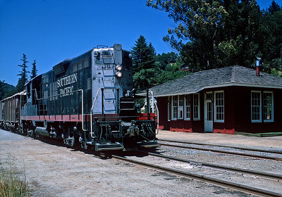 Circa 1958.  A loaded sand train passes the Felton depot on its way downhill to Santa Cruz.