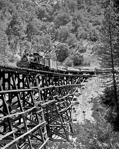 "A ""down"" train of logs crosses River Bridge. The working side of the shays was always on the dark side when hauling loads across the bridge.  October 1960."