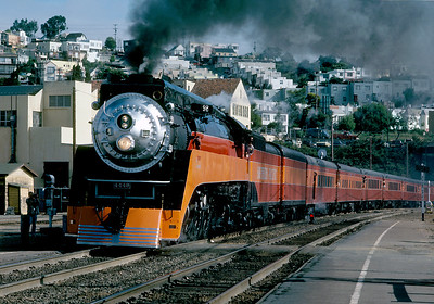 """May 1984.  The 4449 with the New Orleans Worlds Fair Daylight departs San Francisco on the original route of the Coast Daylights for which it was built. Note in the background the """"little boxes on the hillside"""" of Pete Seeger fame."""
