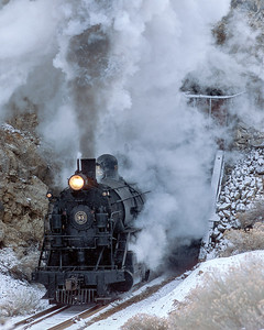 January 2000.  On a frigid winter morning a train of empty ore cars heads up the hill and through Tunnel One for the mines around Copper Flat, where they will be loaded back to the mill at McGill. Or at least this is a 2000 recreation of such an operation. Joel Jensen was in charge of the Nevada Northern winter photo shoots in those days and arranged for 93 to be relettered for K.C.C. As corrected from the comment below, I understand the 93 is lettered for N.C.C.Co (not K.C.C.) for this year's winter photo events. It was originally an N.C.C.Co (Nevada Consolidated Copper Company) engine before Nevada Consolidated was absorbed by Kennecott. Nevada Northern ran the common carrier line from Ely to connections with the WP and SP, NCCCo and then KCC ran the ore line from the mines to the smelter. The annual NN winter photo shoots have been going on for over ten years, and just keep getting more popular. And the date is 2000 not 2003 as originally posted.