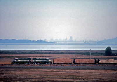 A Lombard bound train crosses the wetlands east of the Black Point bridge with the Richmond San Rafael bridge and San Francisco skyline in the distance.