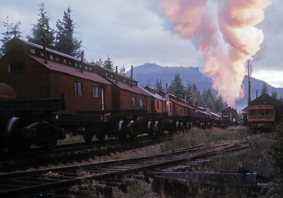 "July 1961.  With the first rays of an early morning sun illuminating a split smoke plume, a train of empty log cars pulls into Camp 14 on the Rayonier Hoquiam logging line. Of particular interest in this view are the ""camp cars"" in the background, mounted on bogies and moved by rail as needed (although I would guess clearances where a challenge). Several of the camp cars have been saved and are at a museum in Tacoma. This is another of my old Anscochromes saved by Photoshop."