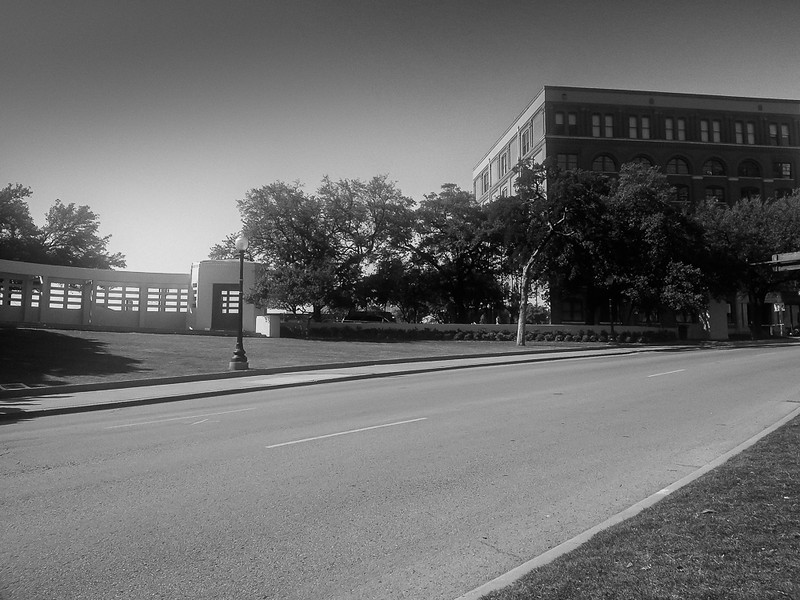Site of the JFK assassination, Dallas. Texas Book Depository on the right, the edge of the grassy knoll on the left.