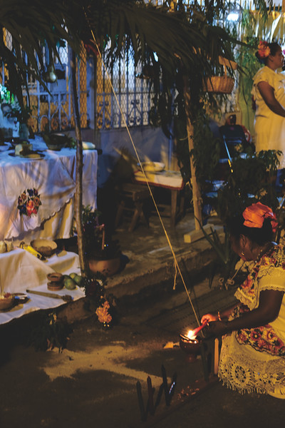 Lighting candles at a Hanal Pixan altar. October 2018
