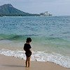 Kid playing by Waikiki beach, Diamond head in the background